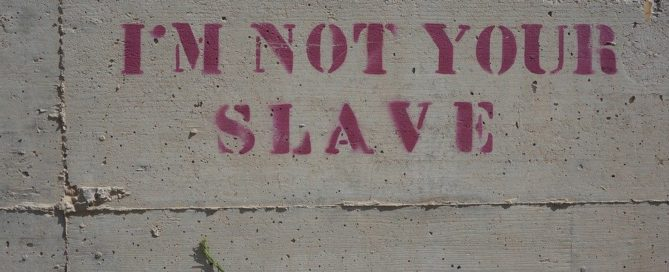 "Concrete wall with ""I'm Not Your Slave"" stenciled on it"