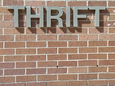 "Sign displaying the word ""thrift"" on a brick wall"